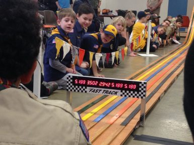Scouts from Pack 109 watch as their Pinewood Derby cars cross the track. | Photo courtesy of Ken Snyder