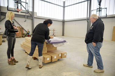From left, Jenny Shepherd, Rachel Entler and Larry Piekarz look at the new purple gym mats. | Alexa Rogals/Staff Photographer