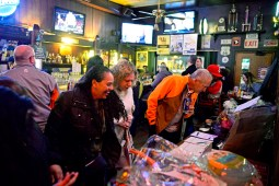 Customers look through the silent auction items during the Forest Park for Puerto Rico fundraiser party at McGaffer's Saloon on Roosevelt Road. | Alexa Rogals/Staff Photographer