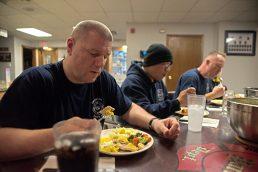 Firefighter Mark Maylath, left, eats dinner with the crew after a call. | Alexa Rogals/Staff Photographer
