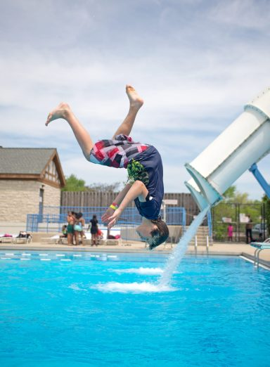 Seventh grader Calvin Grzelak does a back flip off of the diving board on Thursday, May 17, during the annual D91 All School Picnic at the Park District of Forest Park on Harrison Street. Students play on the inflatable slides.   Alexa Rogals/Staff Photographer