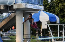Jamarrion Peterson does a dive off the dive board during the annual Juneteenth Pool Party at the Aquatic Center in Forest Park. Photo by William Camargo