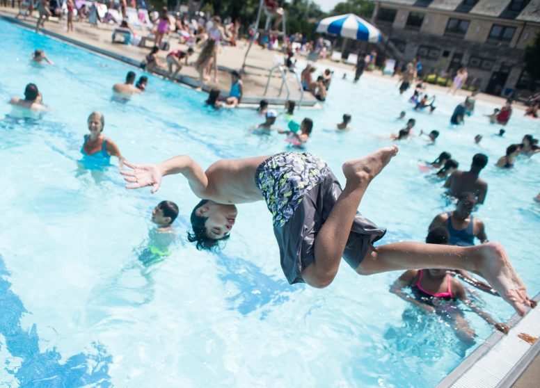 Children do flips as they jump into the water on Saturday, Aug. 4, at the Forest Park Aquatic Center on Harrison Street. | Alexa Rogals/Staff Photographer