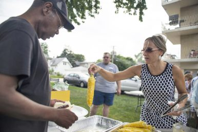 Elise Dalton, of Brookfield, serves up fresh cooked corn on Saturday, Aug. 11, during a free corn boil at St. John's Community Gardens in Forest Park. garden.   Alexa Rogals/Staff Photographer