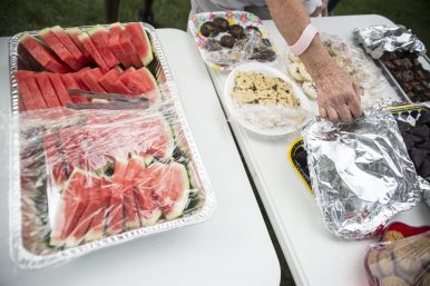 Attendees enjoy a variety of desserts and fruit including watermelon. under a tent near the garden on Saturday, Aug. 11, during a free corn boil at St. John's Community Gardens in Forest Park.   Alexa Rogals/Staff Photographer