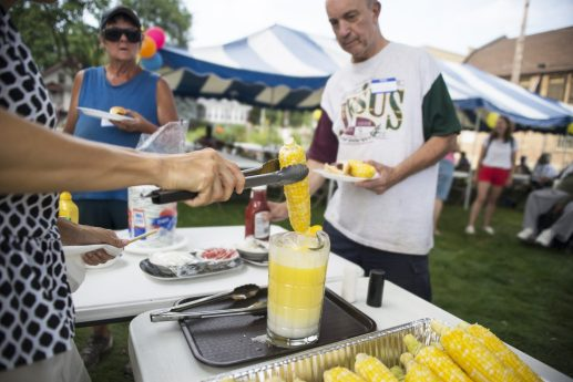 Elise Dalton, of Brookfield, dips corn into melted butter on Saturday, Aug. 11, during a free corn boil at St. John's Community Gardens in Forest Park.   Alexa Rogals/Staff Photographer