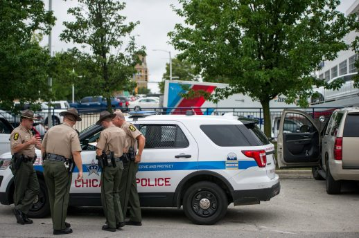 A group of Illinois State Police officers talk near a Chicago Police vehicle on Wednesday, Aug. 29, 2018, in the parking lot at the United States Postal Service building on Garfield Street near Harlem Avenue in Oak Park, Ill. (ALEXA ROGALS/ Staff Photographer)