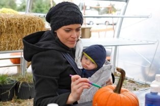 Hannah Bentley, of Oak Park, paints a pumpkin Oct. 20 as four-month-old Graham looks on at McAdam Landscaping Professionals. | Sarah Minor/Contributor