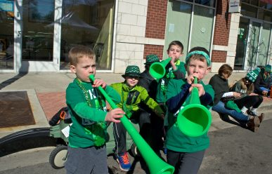 Parade-goers play with blow horns on Saturday, March 3, 2018, during the annual Saint Patrick's Day Parade on Madison Street. | Alexa Rogals/Staff Photographer