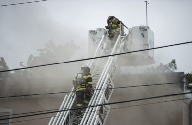 A Forest Park firefighter climbs to the roof with a chainsaw on Thursday, Jan. 10, 2019, on Hannah Avenue at the corner of Roosevelt Road in Forest Park, Ill. | ALEXA ROGALS/Staff Photographer