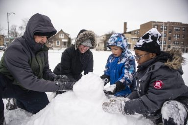 From left, Hadid Morales, Jeanette Brink, Eddy Morales and Mickey Foster, all of Forest Park, attempt to build a snowman from the ground up. | Alexa Rogals/Staff Photographer
