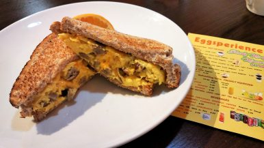 Cheddar cheese and sausage snuggle up with scrambled eggs on 9-grain bread at Eggsperience.