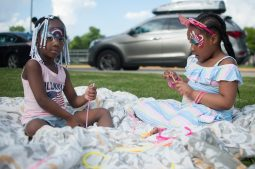 Daniya Jones and Jayla Stepney both of Chicago preparing their glow stick bracelets and necklaces for the evening fireworks. | SHANEL ROMAIN/Contributor