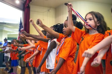 "Scholars sing and dance to ""Baby Shark"" during the Power Scholars Academy closing ceremony at Forest Park Middle School. 