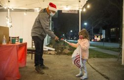 Fiona Fustar, 5, delivers gifts to Mayor Rory Hoskins at the toy drive on Dec. 18. | Alex Rogals, Staff Photographer