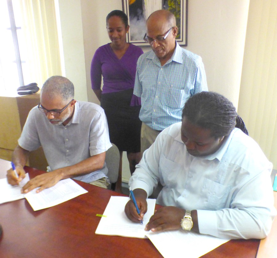 (Front) Joslyn McKenzie (right) and TCG's Timothy McIntosh signing the contract. (from back)FCPF Project Coordinator Clayton Hall (standing at right) and Project Assistant Michelle Astwood