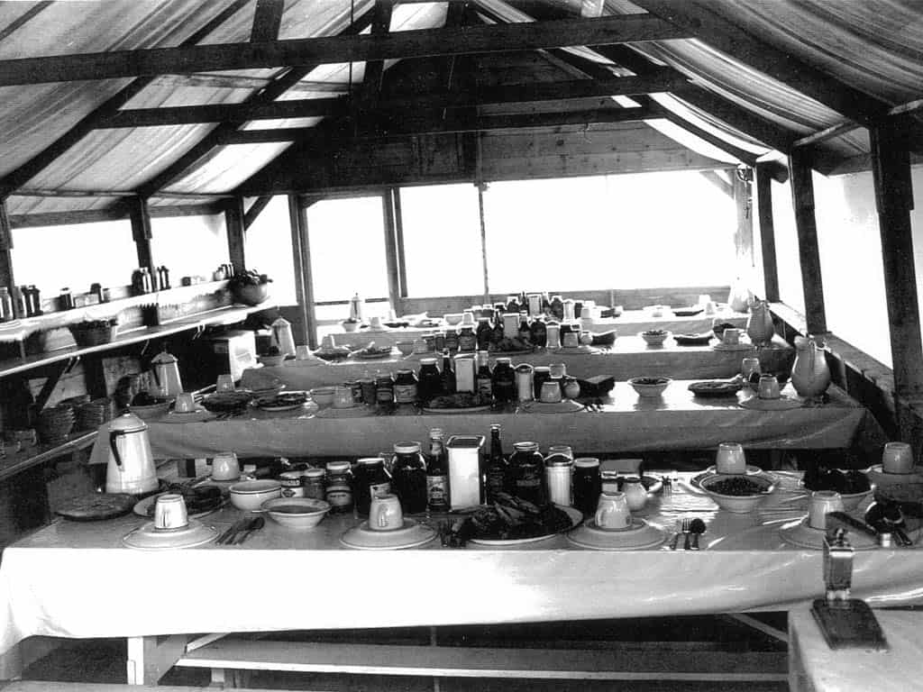 Tables set for dinner with Forest Service logo dishware in a field mess tent, c 1935. Two pies are on the end of each table and a wall telephone is visible. The photo was most likely taken at a blister rust control camp, which was a New Deal-era program for the Civilian Conservation Corps (CCC).