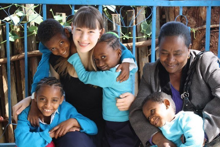 Abby pictured with children in their school uniforms.