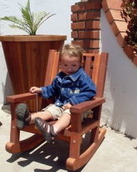 Little Raulito enjoying a Forever Redwood Kids Rocking Chair. Behind him stands a Vase Planter. Proceeds from the sale of Forever Redwood go toward Redwood forest restoration work.