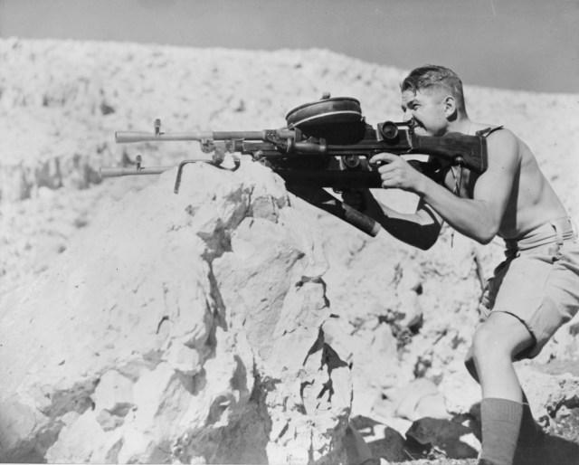 New Zealand trooper firing a pair of Bren guns with 100-round drum mags