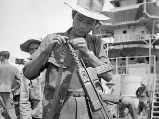 Vietnamese soldier in French service working on his MAT-49 SMG.