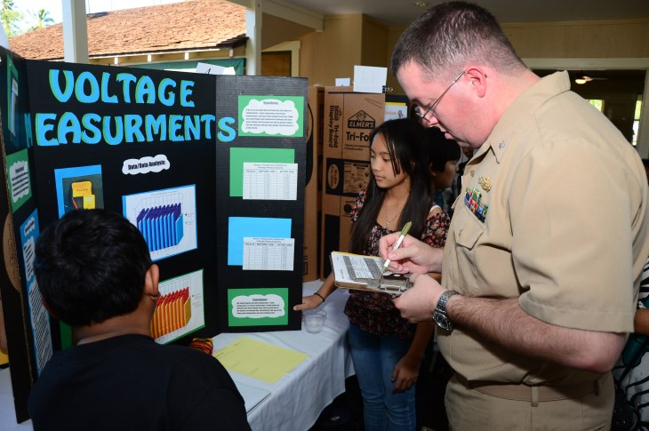 Cmdr. Tom Mays, assigned to the Pacific Missile Range Facility (PMRF), judges the science fair project of 7th graders Cody Argaho and Jayda Oyamot. PMRF Sailors joined over 20 volunteeres as judges for the Waimea Canyon Middle School Science Fair. (U.S. Navy Photo by Mass Communication Specialist 2nd Class Mathew J. Diendorf/Released)
