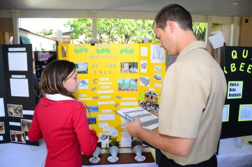 Logistics Specialist 2nd Class Brandon Healy, assigned to the Pacific Missile Range Facility (PMRF), evaluates a Waimea Canyon Middle School student's science fair project. PMRF Sailors joined over 20 volunteers as judges for the Waimea Canyon Middle School Science Fair. (U.S. Navy Photo by Mass Communication Specialist 2nd Class Mathew J. Diendorf/Released)