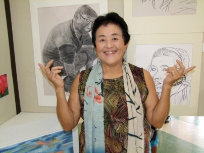Beginning Drawing instructor Carol K. Yotsuda with some of her students' work