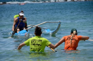 Paddlers in the two-man outrigger division surge through the Po`ipu water to switch partners with teammates during last year's Kaua`i World Challenge. Photo by Kathleen Ho