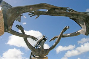 Three hula dancers hold hands in Ken Shutt's sculpture in front of Kauaʻi Community College Performing Arts Center.
