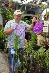 "Neill Sams, owner of Orchid Alley Kaua'i in Old Kapa'a Town, has been growing orchids for at least 25 years. Here, he is holding two champions from the last Mothers' Day Show by the Kaua'i Orchid Society. The Vanda Coerulea, on the left, took ""Best in Show"" and also an ""Award of Merit"" from the American Orchid Society, and a cross from the Vanda Manuvadee and Vanda Coerulea took ""Best Purple."" Visit www.orchidalleykauai.com or call 822-0486 for more information."