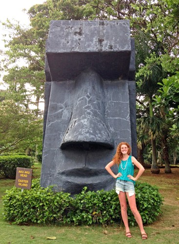 An Easter Island's aku aku head replica at Smith's Tropical Paradise in Wailua dwarfs Utah visitor Hayden Merritt. No one can say for sure how and why the Easter Islander natives erected those giant stone statues. Not too long ago, archaeologists discovered the heads have bodies attached to them, hidden underground. Photo by Halli Holmgren.