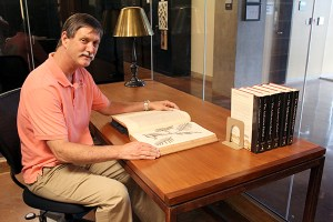 Inside NTBG's library, Chipper Wichman holds a book written in the 1600s and published in the 1700s.