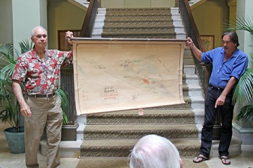 Bill Fernandes, left, and Randy Wichman hold a 1913 Kekaha Sugar Co. map in the main hall of the Historic County Building March 6.