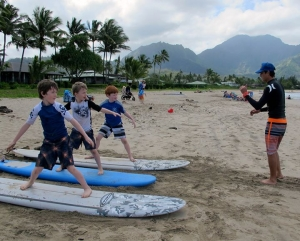 Evan Valiere, owner of Hanalei Surf School, is seen here teaching the basics of surfing before students get into the water at Hanalei Bay.