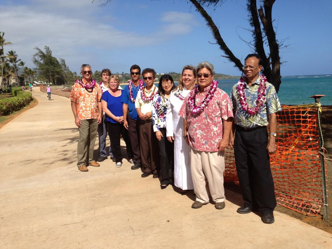 County officials and representatives of Goodfellow Brothers, Pono Kai Resort and Oceanit Laboratories pose for a photo following the blessing of the Pono Kai seawall repair project. L to R: Larry Dill, County Engineer; Doug Haigh, Building Division Chief; Connie Meyer, Project Manager, Goodfellow Bros.; Steven Pimental, Grounds Manager, Pono Kai Resort; Peter Sit, General Manager, Pono Kai Resort; Nadine Nakamura, Managing Director; Kahu Jade Battad; Lyle Tabata, Deputy County Engineer; and Dayan Vithanage, Oceanit Laboratories.