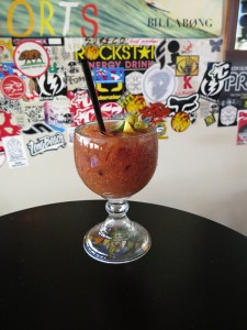 A classic Bloody Mary, spicy and strong, sitting before a wall of surf stickers and posters. The bar also serves a large range of draft beers.