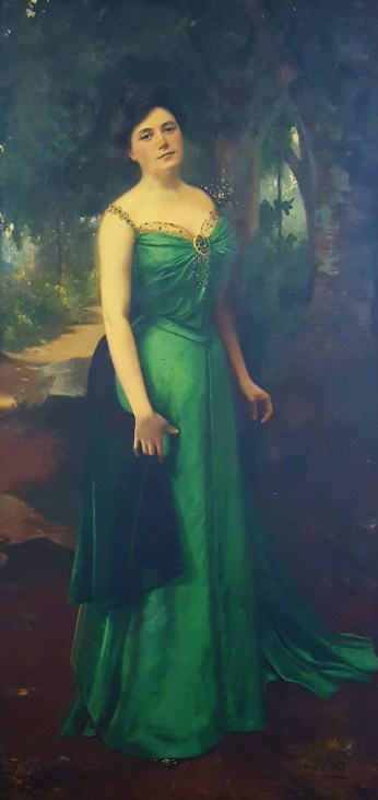 An oil painting by Hubert Vos of his wife Kaikilani, done in the gardens of her Nawiliwili home in 1900. The painting was donated in 1997 to the Kaua'i Historical Society, where it hangs in the entryway.
