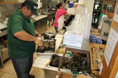 Rob Kubota is the third generation of the Kubota family working at Pono Market in Kapa'a. Here he is seen getting the lau lau ready just prior to lunch time.