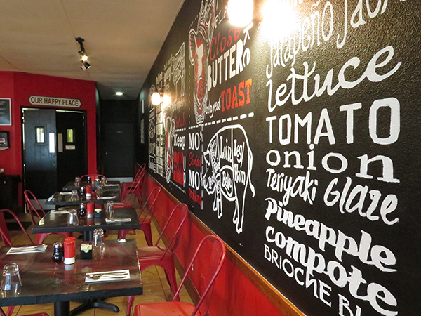 NOM's happy place is dominated by a wall full of ingredients and catchy phrases to keep your breakfast, brunch and lunch entertained.