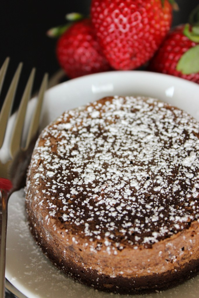 molten chocolate cake with strawberries and powdered sugar