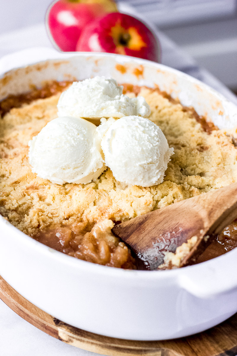 apple crisp in baking dish with spoon and ice cream on top