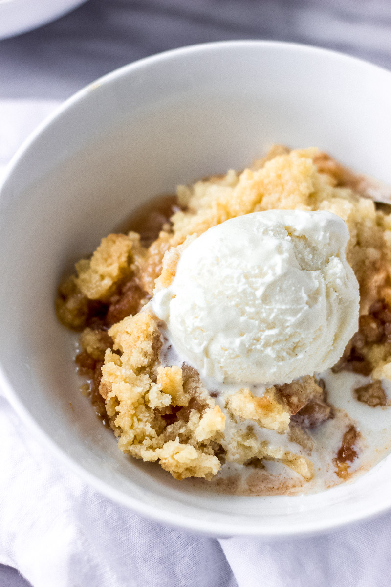 bowl of apple crisp with spoon and ice cream