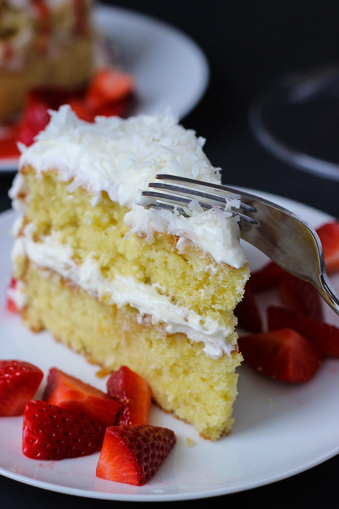 Strawberry Coconut Cake - moist, heavenly cake with a creamy coconut frosting, topped with fresh strawberries and a strawberry sauce!