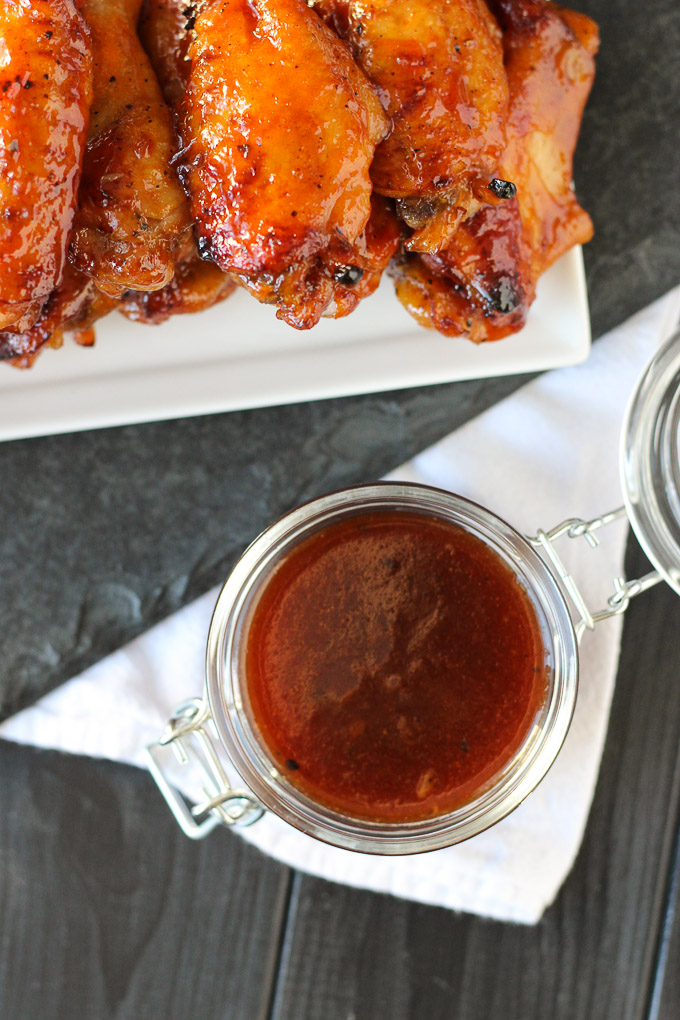 overhead view of bbq sauce in jar next to chicken wings