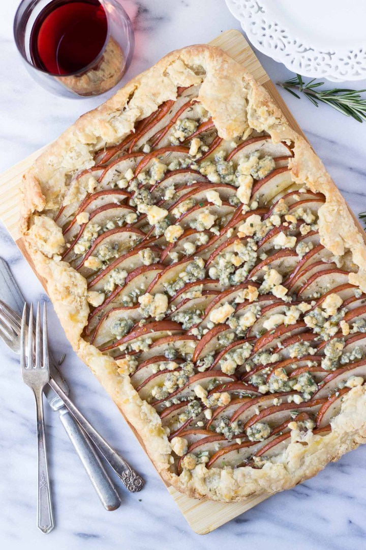 Savory Pear Tart - a flakey crust topped with Bosc pears, rosemary, gorgonzola, and drizzled with honey for the delicate balance of sweet and savory! Excellent for a night-in with wine or as a holiday appetizer.