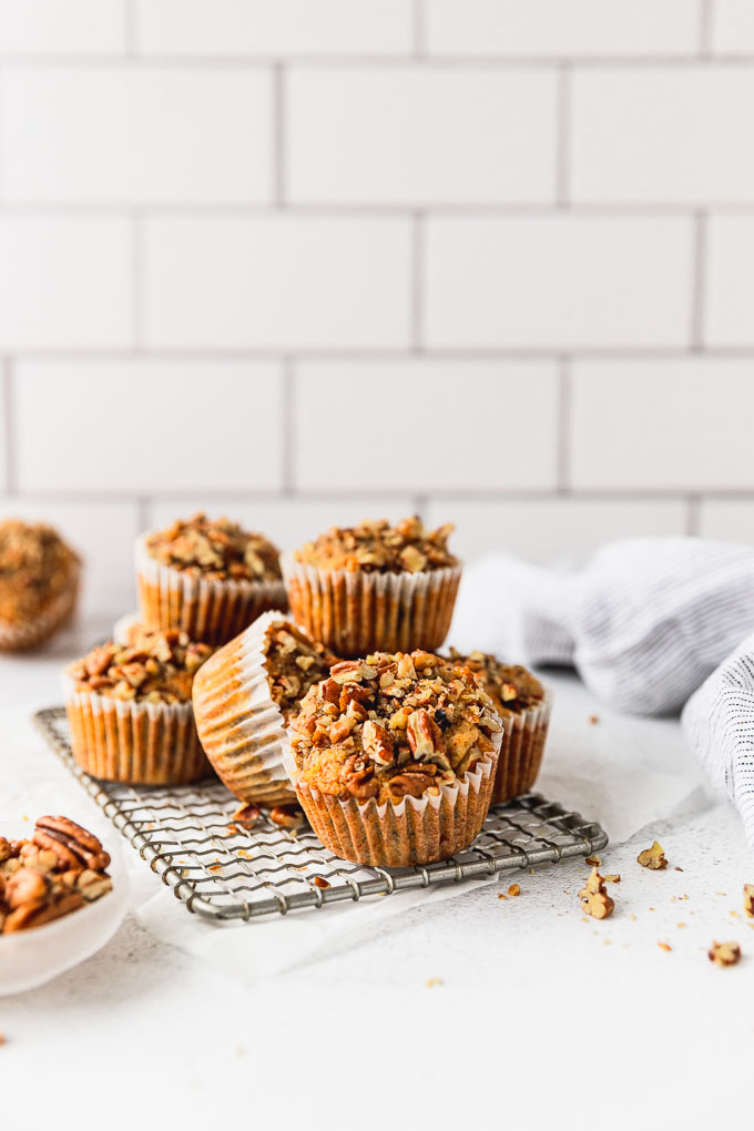 banana carrot muffins stacked on cooling rack  next to linen