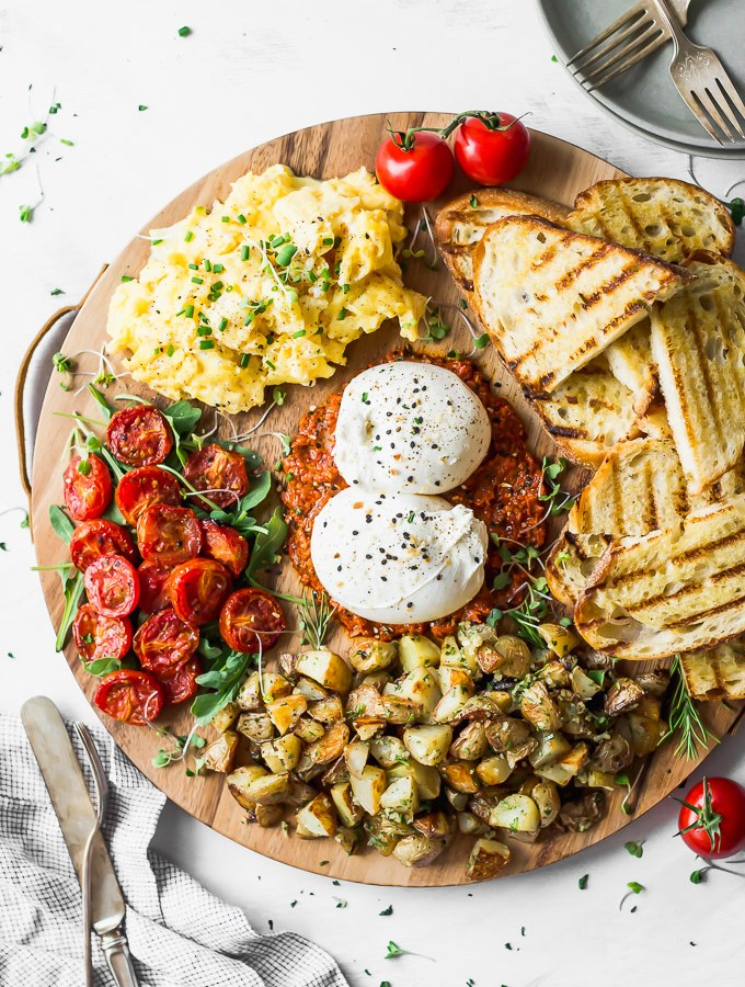 round wood board filled with burrata, tomatoes, potatoes, toast, and eggs alongside silverware