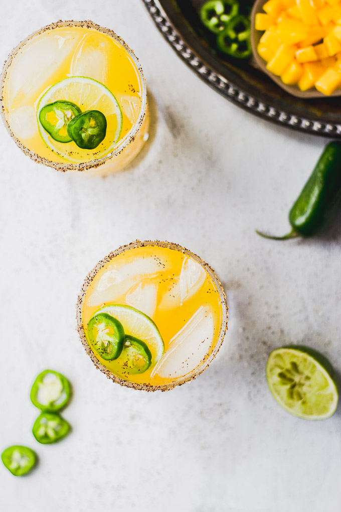 overhead mango margaritas with pepper salt rim, jalapenos, and lime next to platter