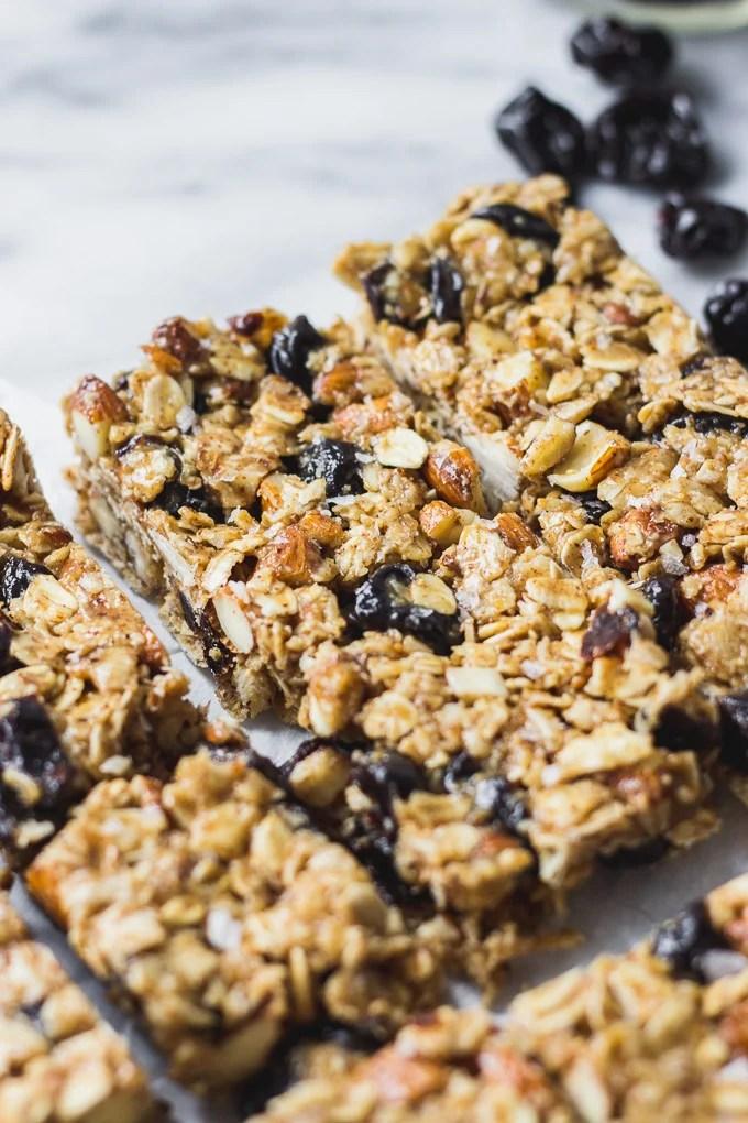 close up cherry almond granola bars on white background